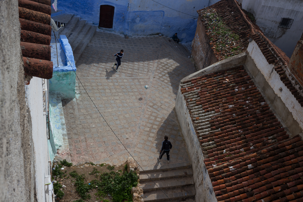 Two Moroccan boys play soccer in a small plaza in Chefchaouen.